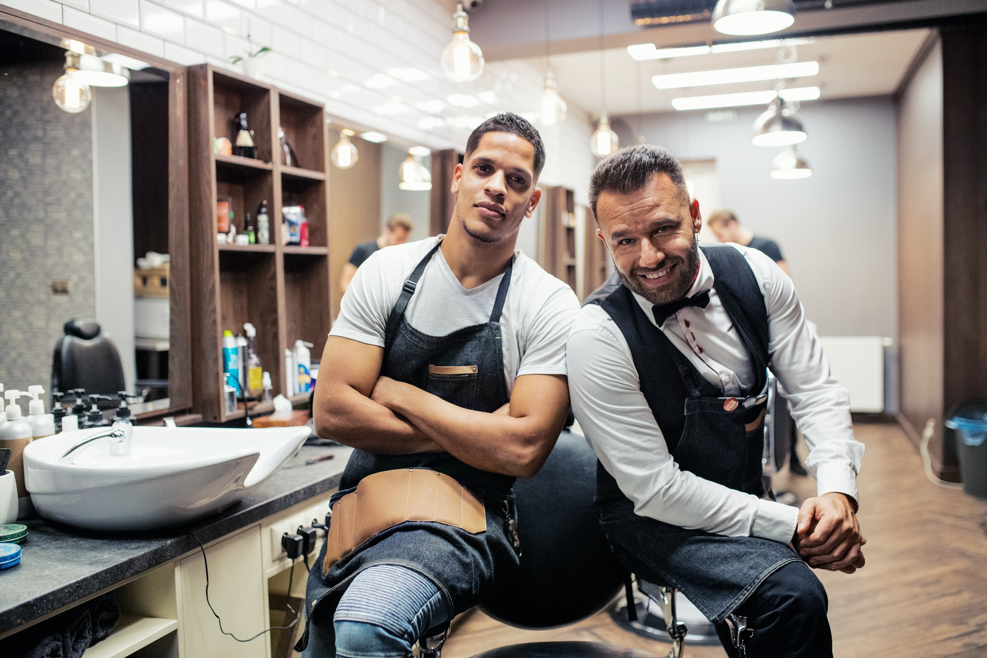 Two male haidressers and hairstylists sitting in barber shop.